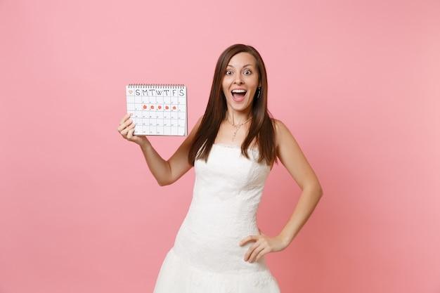 Zaskoczona kobieta w białej sukni trzymająca kalendarz kobiecych miesiączek do sprawdzania dni menstruacyjnych