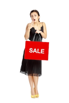 Zaskoczona kobieta w czarnej sukni z torby na zakupy na białym tle.