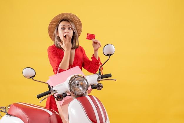 Zaskoczona kobieta w czerwonej sukience na motorowerze trzymająca torby na zakupy i kartę kredytową