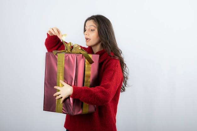 Zaskoczona kobieta w czerwonym swetrze otwierająca pudełko z prezentami świątecznymi.