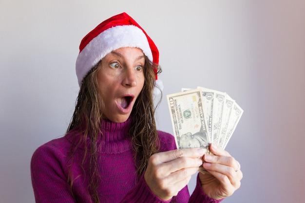 Zaskoczona kobieta w świątecznym kapeluszu trzymająca banknoty dolarowe na białym tle