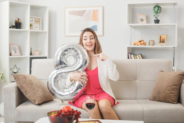 Zaskoczona kobieta w szczęśliwy dzień kobiet trzymająca i wskazująca na balon numer osiem siedząca na kanapie w salonie