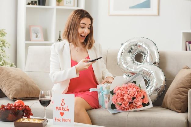 Zaskoczona kobieta w szczęśliwy dzień kobiet trzymająca telefon siedząca na kanapie w salonie