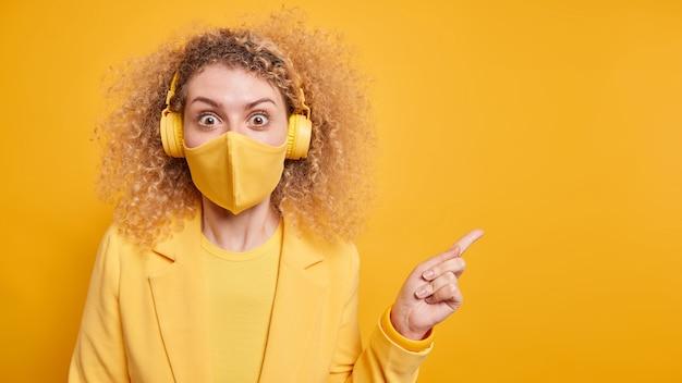 Zaskoczona kobieta z kręconymi włosami wskazuje na przestrzeń kopii, zafascynowana czymś niesamowitym, nosi bezprzewodowe słuchawki do słuchania muzyki maskę ochronną podczas epidemii koronawirusa
