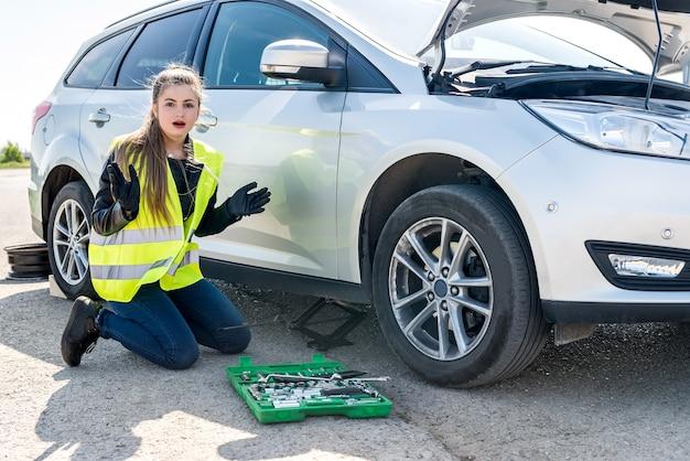 Zaskoczona kobieta z narzędziami i zepsutym samochodem na poboczu