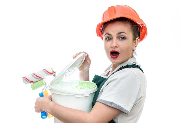 Zaskoczona kobieta z wiadrem z farbą i narzędziami do malowania