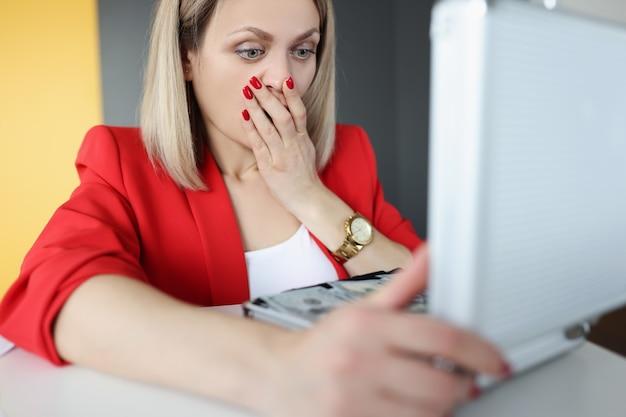 Zaskoczona kobieta zaglądająca do otwartej walizki z pieniędzmi i zakrywająca usta dłonią