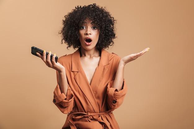 Zaskoczona ładna afrykańska kobieta trzymająca smartfon i patrząca bezpośrednio z otwartymi ustami na brązowym tle