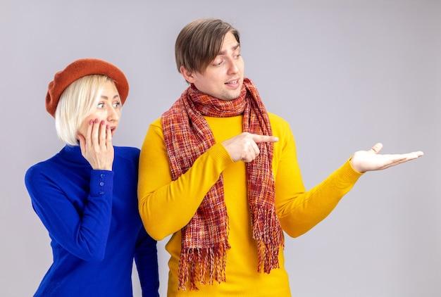 Zaskoczona ładna blond kobieta z beretem patrząca na rękę przystojnego słowiańskiego mężczyzny z szalikiem wokół szyi na białym tle na białej ścianie z kopią przestrzeni