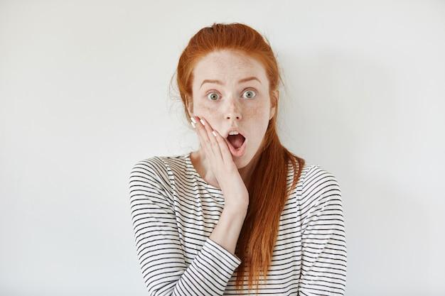 Zaskoczona ładna dziewczyna z rudymi włosami trzymająca dłoń na policzku i szeroko otwierająca usta, nie może uwierzyć własnym oczom, krzycząca z szoku i pełnego niedowierzania