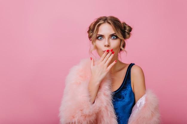 Zaskoczona ładna dziewczyna z uroczą fryzurą powiedziała coś nie tak, pozując przed różową ścianą. urocza młoda kobieta w aksamitnym body zakrywa usta ręką, na białym tle na jasnym tle