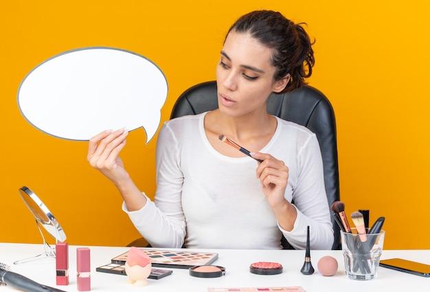 Zaskoczona ładna kaukaska kobieta siedzi przy stole z narzędziami do makijażu, trzymając pędzel do makijażu i patrząc na dymek