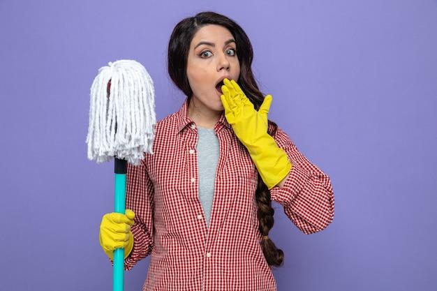 Zaskoczona ładna kaukaska sprzątaczka w gumowych rękawiczkach, trzymająca mopa i kładąca dłoń na ustach