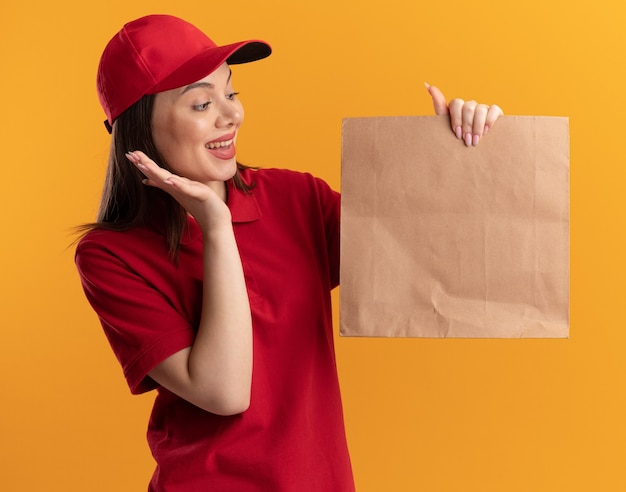 Zaskoczona ładna kobieta dostarczająca w mundurze stoi z podniesioną ręką trzymająca i patrząca na papierowy pakiet odizolowany na pomarańczowej ścianie z miejscem na kopię
