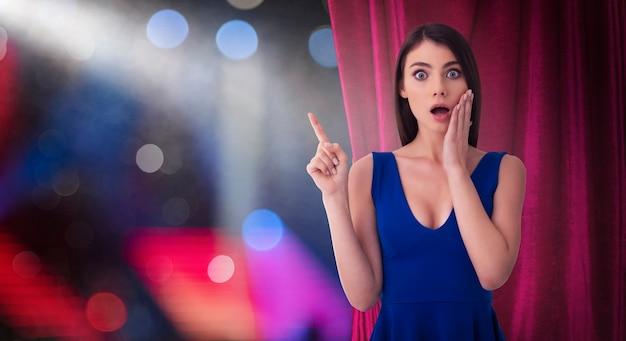 Zaskoczona ładna kobieta przed czerwonymi zasłonami wskazuje na coś na temat spektaklu teatralnego