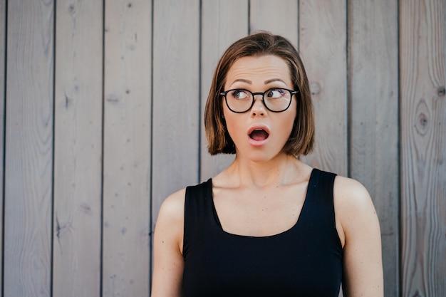 Zaskoczona ładna krótkowłosa dziewczyna w okularach, ubrana swobodnie z szeroko otwartymi oczami i ustami, patrząc na bok na pustą przestrzeń nad drewnianą ścianą. koncepcja emocje ludzi. obroty