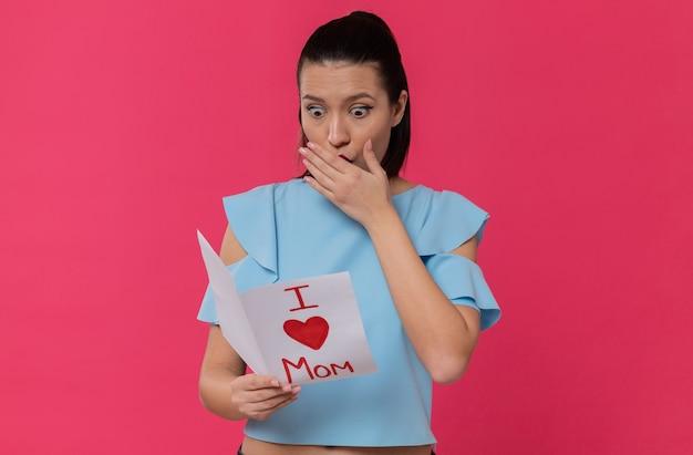 Zaskoczona ładna młoda kobieta czyta list od swojego dziecka