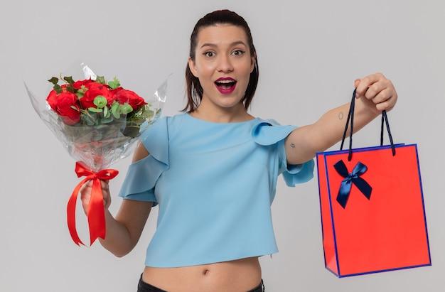 Zaskoczona ładna młoda kobieta trzyma bukiet kwiatów i torbę na prezent