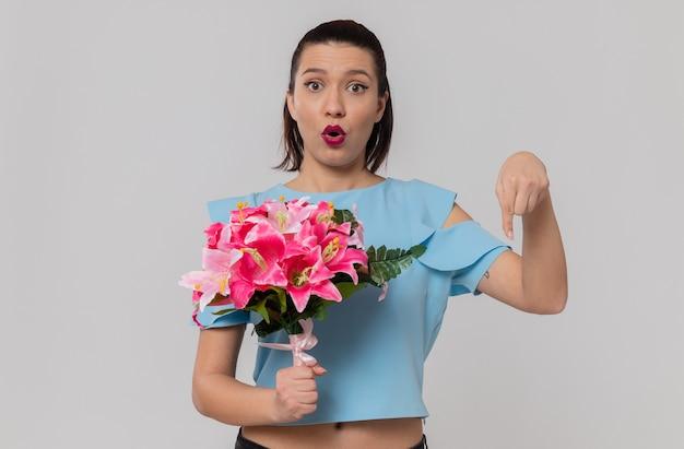 Zaskoczona ładna młoda kobieta trzymająca bukiet kwiatów i wskazująca w dół