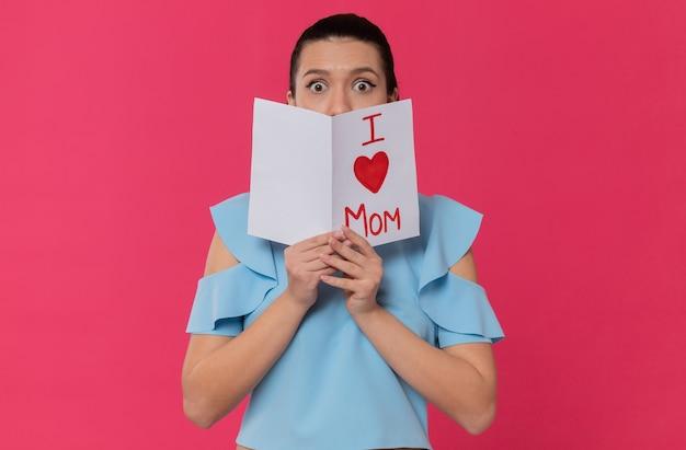 Zaskoczona ładna młoda kobieta trzymająca list od dziecka
