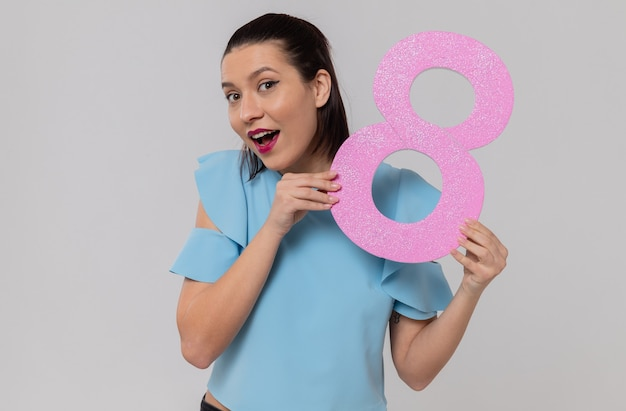Zaskoczona ładna młoda kobieta trzymająca różowy numer osiem