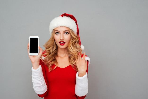 Zaskoczona ładna młoda kobieta w stroju noworocznym i kapeluszu pokazująca pusty ekran telefonu komórkowego na szarej powierzchni