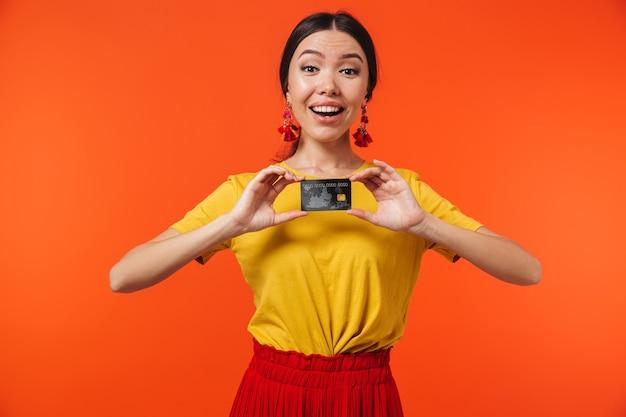 Zaskoczona latynoska 20-latka ubrana w spódnicę uśmiechnięta i trzymająca kartę kredytową odizolowaną od czerwonej ściany