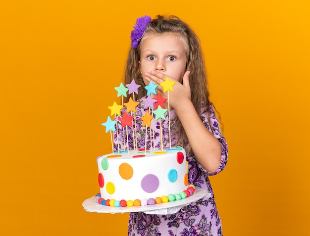 Zaskoczona mała blondynka trzymająca tort urodzinowy i kładąca dłoń na ustach na pomarańczowej ścianie z miejscem na kopię with