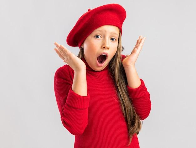 Zaskoczona mała blondynka ubrana w czerwony beret trzymając puste ręce w górze, patrząc z przodu z otwartymi ustami na białym tle na białej ścianie z miejscem na kopię copy