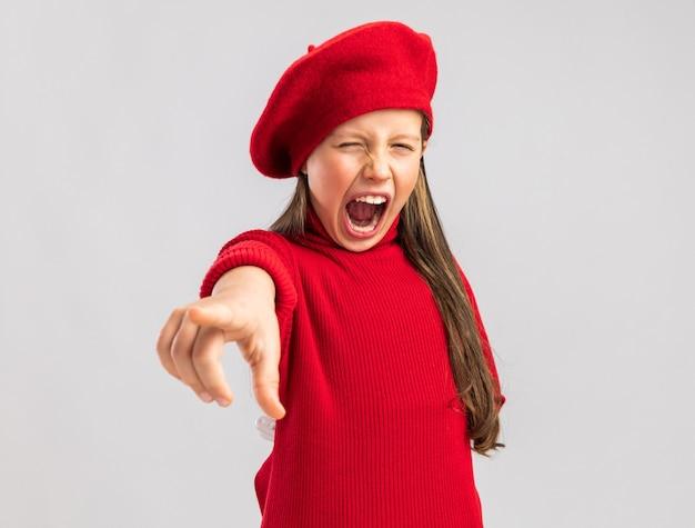 Zaskoczona mała blondynka ubrana w czerwony beret wskazujący i odizolowana na białej ścianie z miejscem na kopię