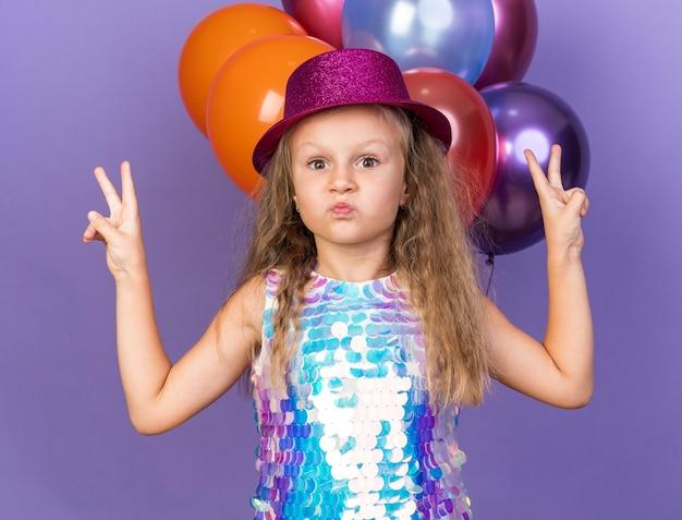 Zaskoczona mała blondynka w fioletowym kapeluszu imprezowym gestykulującym znakiem zwycięstwa stojącym przed balonami z helem odizolowanymi na fioletowej ścianie z kopią przestrzeni