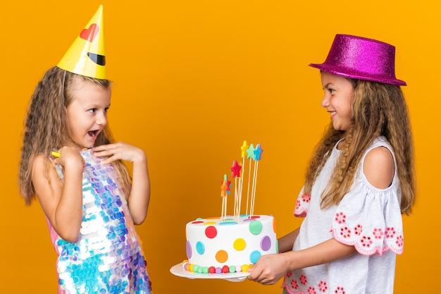 Zaskoczona mała blondynka w imprezowej czapce patrząca na małą kaukaską dziewczynkę w fioletowym kapeluszu trzymającym tort urodzinowy na pomarańczowej ścianie z kopią miejsca