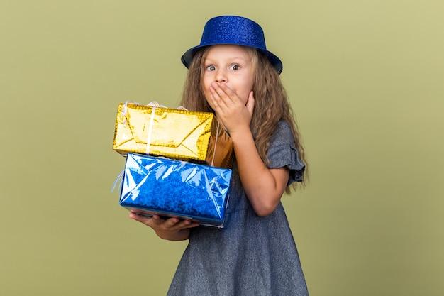 Zaskoczona mała blondynka w niebieskim kapeluszu imprezowym, kładąca dłoń na ustach i trzymająca pudełka z prezentami na oliwkowozielonej ścianie z miejscem na kopię