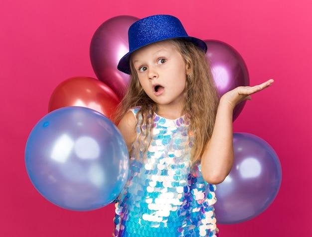 Zaskoczona mała blondynka z niebieskim czapką stojącą z balonami z helem, trzymając dłoń otwartą na białym tle na różowej ścianie z miejsca na kopię