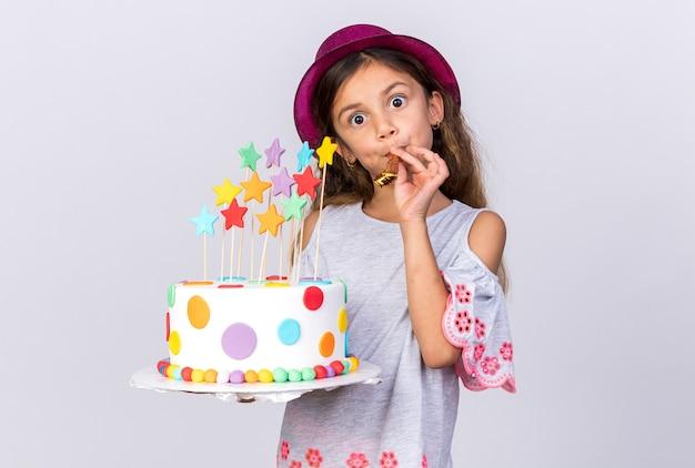 Zaskoczona mała dziewczynka kaukaski z fioletowym kapeluszem strony, trzymając tort urodzinowy i dmuchający gwizdek na białym tle na białej ścianie z miejsca na kopię