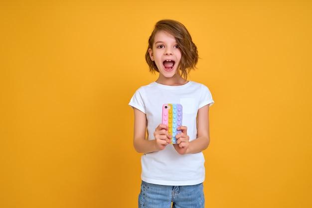 Zaskoczona mała dziewczynka trzymająca telefon z otwartymi ustami na białym tle na pomarańczowym tle