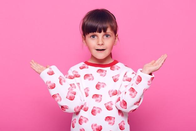 Zaskoczona mała dziewczynka ubiera sweter z sercami, patrząc z przodu z otwartymi ustami, słysząc szokujące wieści, rozkładając ręce na bok, odizolowaną na różowej ścianie