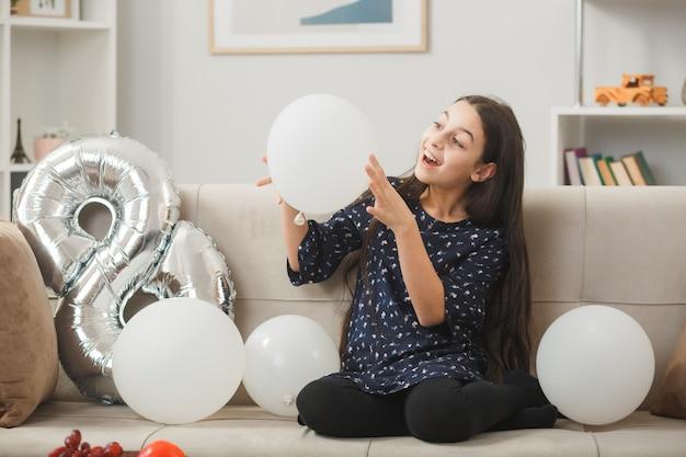 Zaskoczona mała dziewczynka w szczęśliwy dzień kobiety, trzymająca i patrząca na balon siedzący na kanapie w salonie