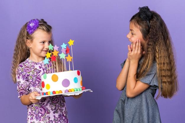 Zaskoczona mała kaukaska dziewczynka patrząca na zadowoloną małą blondynkę trzymającą tort urodzinowy odizolowaną na fioletowej ścianie z miejscem na kopię