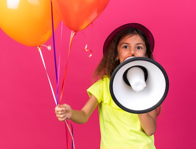 Zaskoczona mała kaukaska dziewczynka w fioletowym kapeluszu imprezowym trzymająca balony z helem i mówiąca do głośnego głośnika odizolowana na różowej ścianie z kopią przestrzeni