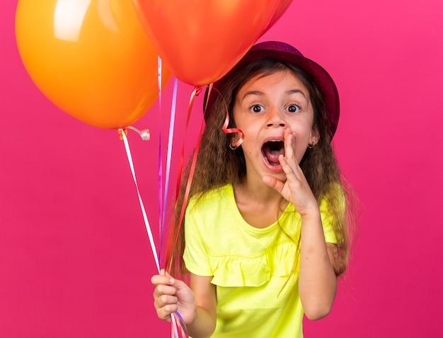 Zaskoczona mała kaukaska dziewczynka w fioletowym kapeluszu imprezowym trzymająca balony z helem i trzymająca rękę przy ustach wołająca kogoś odizolowanego na różowej ścianie z kopią miejsca