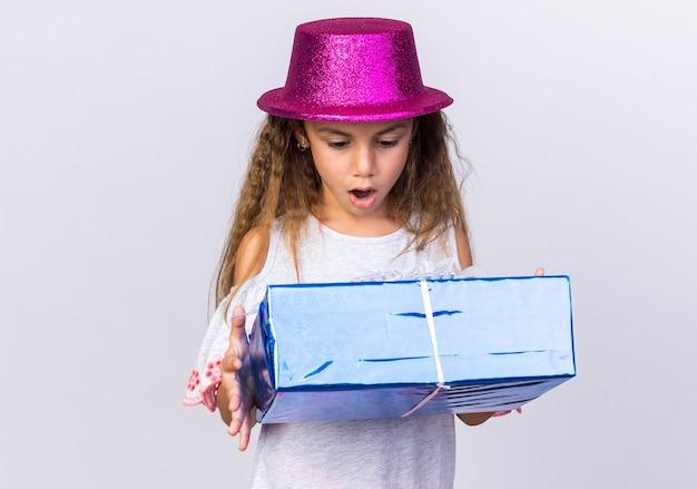 Zaskoczona mała kaukaska dziewczynka w fioletowym kapeluszu imprezowym trzymająca i patrząca na pudełko na białym tle na białej ścianie z miejscem na kopię