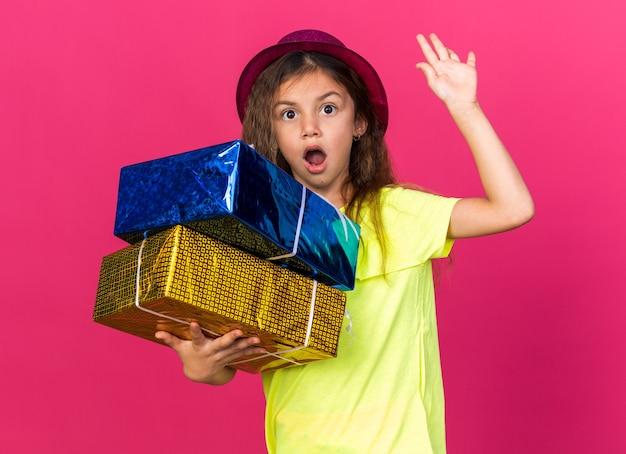 Zaskoczona mała kaukaska dziewczynka w fioletowym kapeluszu imprezowym trzymająca pudełka na prezenty stojąca z podniesioną ręką odizolowana na różowej ścianie z miejscem na kopię
