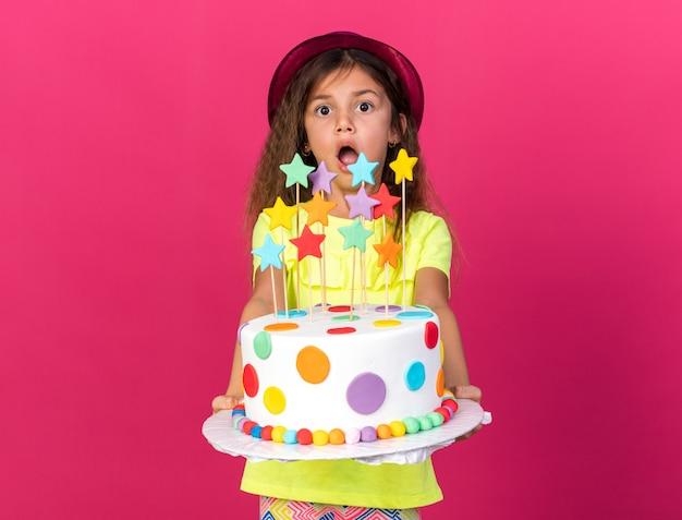 Zaskoczona mała kaukaska dziewczynka w fioletowym kapeluszu imprezowym trzymająca tort urodzinowy na różowej ścianie z miejscem na kopię