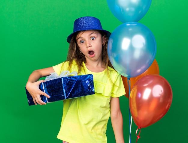 Zaskoczona mała kaukaska dziewczynka w niebieskim kapeluszu imprezowym trzymająca balony z helem i pudełko na prezent na zielonej ścianie z miejscem na kopię
