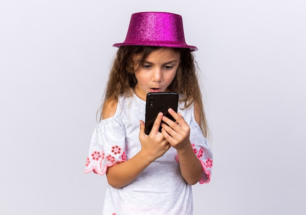 Zaskoczona mała kaukaska dziewczynka z fioletowym kapeluszem trzymająca i patrząca na telefon odizolowany na białej ścianie z miejscem na kopię