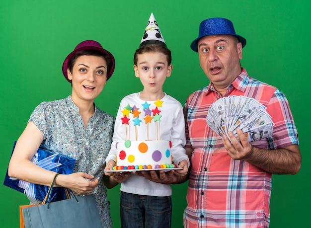 Zaskoczona matka w fioletowym kapeluszu imprezowym, trzymająca pudełko i torby na zakupy, stojąca z synem w czapce imprezowej i trzymająca tort urodzinowy, a ojciec w niebieskiej czapce imprezowej i trzymający pieniądze
