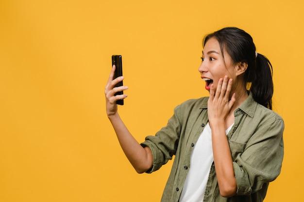 Zaskoczona młoda azjatycka dama korzystająca z telefonu komórkowego z pozytywnym wyrazem twarzy, uśmiecha się szeroko, ubrana w codzienną odzież i stoi na białym tle na żółtej ścianie. szczęśliwa urocza zadowolona kobieta raduje się sukcesem.