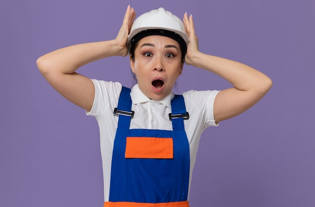 Zaskoczona młoda azjatycka dziewczyna konstruktora kładąca ręce na białym kasku ochronnym
