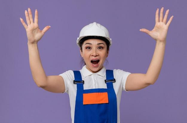 Zaskoczona młoda azjatycka dziewczyna konstruktora z białym kaskiem stojąca z uniesionymi rękami